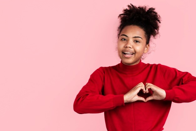 Smiling woman making heart-shaped hands Free Photo